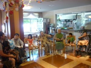 おじいちゃん、おばあちゃんの間に子供たちが座っています。
